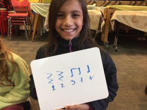 Gilbert Park student holding up whiteboard with music rests and notes