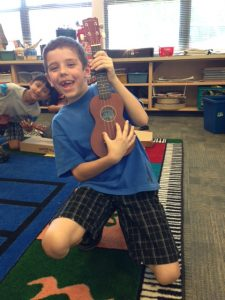 Gilbert Park student grinning and playing ukulele