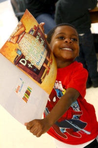 Young boy holding up a children's book
