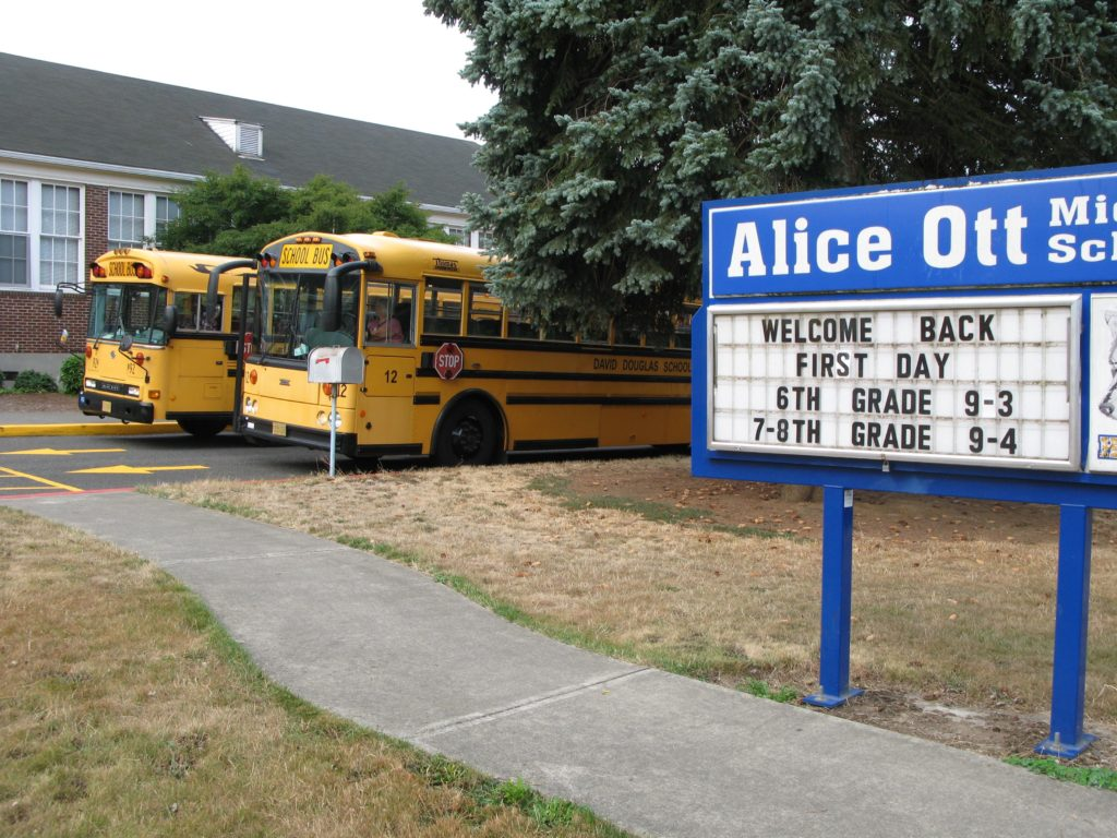 AOMS sign with buses parked in the background
