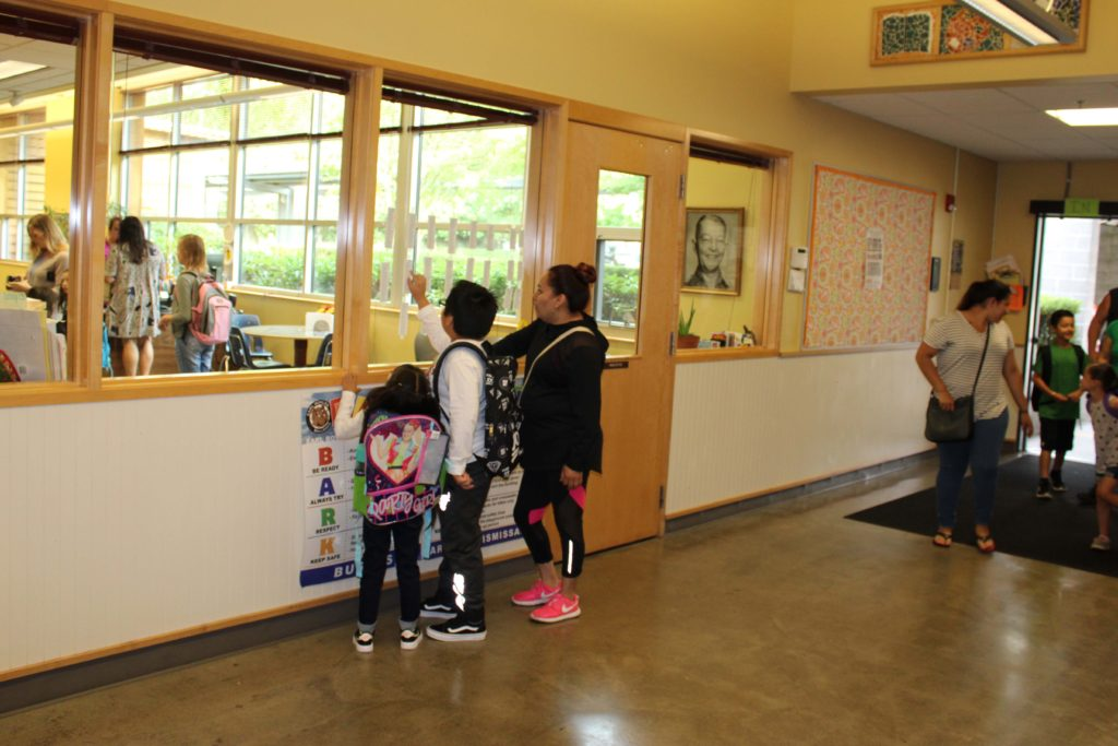 EB Parent and students reading the class lists posted in the lobby
