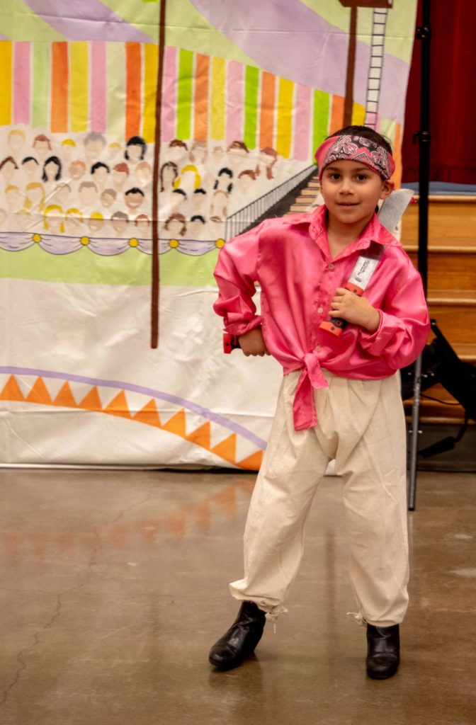 Boy performing at the Earl Boyles Día del Niño (color outfit and backdrop)