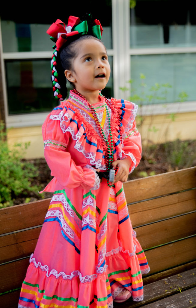 Three year old girl dressed to perform at the Earl Boyles Día del Niño (color dress and hair ribbons)