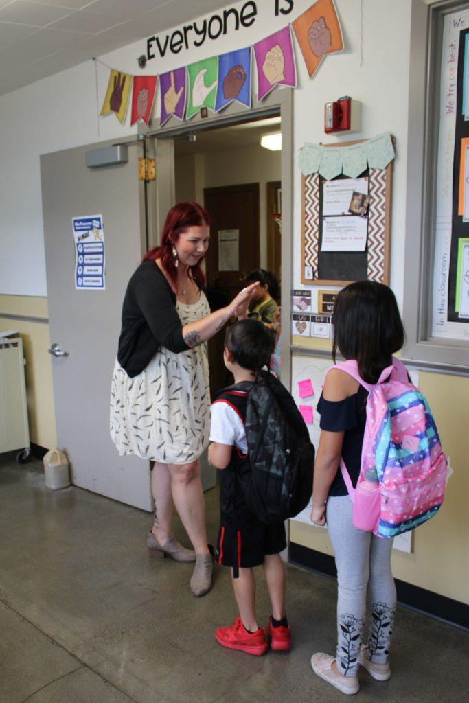 WP teacher welcoming her students at the classroom door