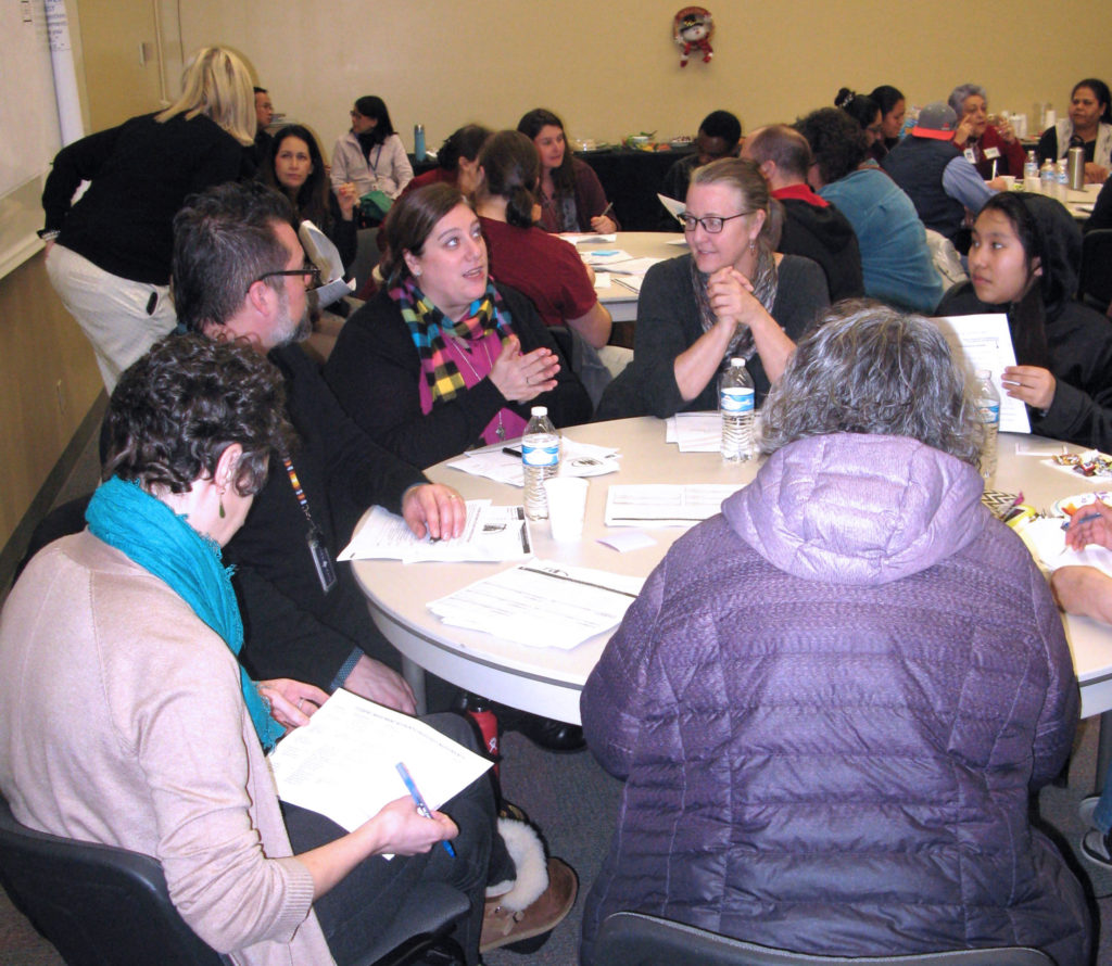 Community Members sitting around a table at the board workshop