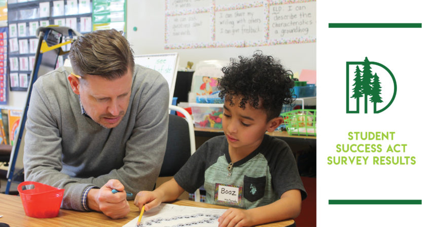 Student working on math at a desk with Education Director Andy Long