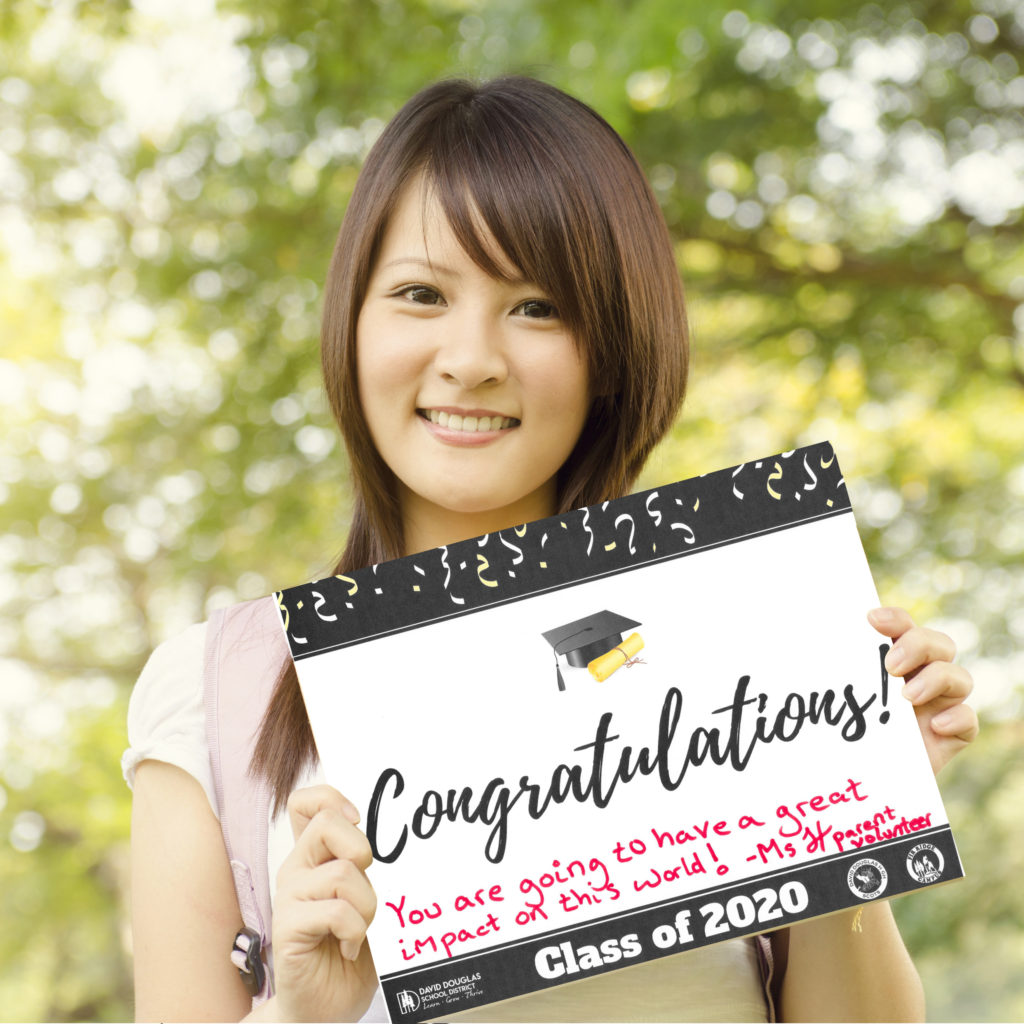 Woman standing outside holding a sample DDSD congrats grad sign