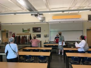 Facilities Planning Committee during building tours. This photo pictures 6 committee members viewing a high school classroom.