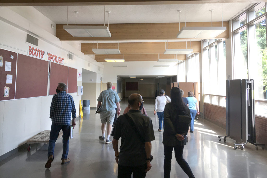 Facilities Planning Committee during building tours. This photo pictures 9 committee members walking down a DDHS hallway (backs to camera).