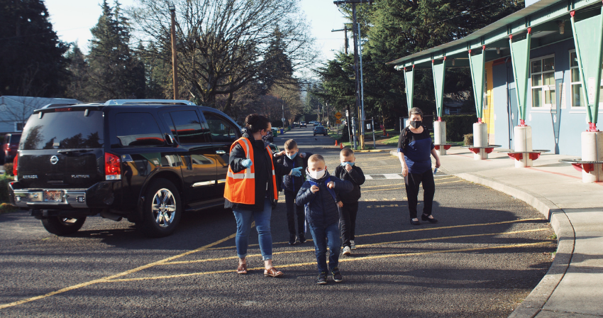Elementary students arriving to school entrance under guidance of crossing guard