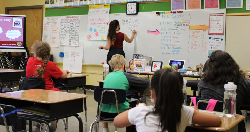 elementary students sitting in class; teacher writing on wipe off board.