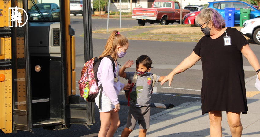 Two students being greeted by a staff member after stepping off of a bus at school
